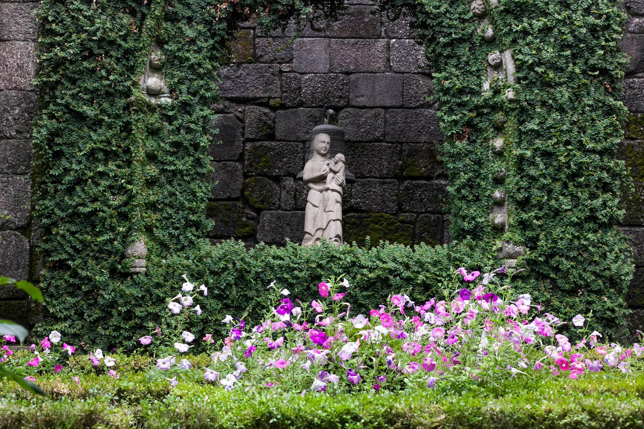 Jardim florido com amores e escultura de Nossa Senhora da Pombinha. Claustro do Museu.