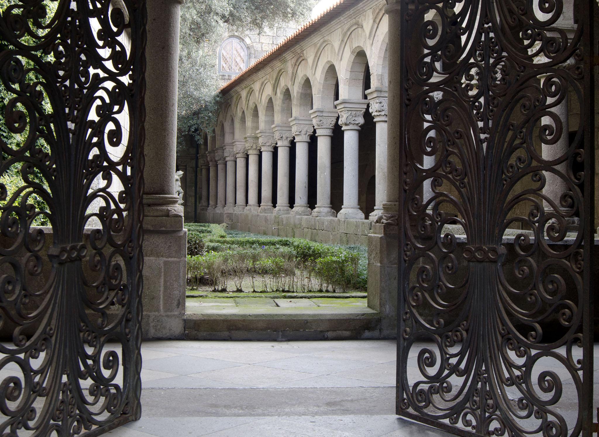 Vista para o interior do claustro, através do portão de ferro forjado