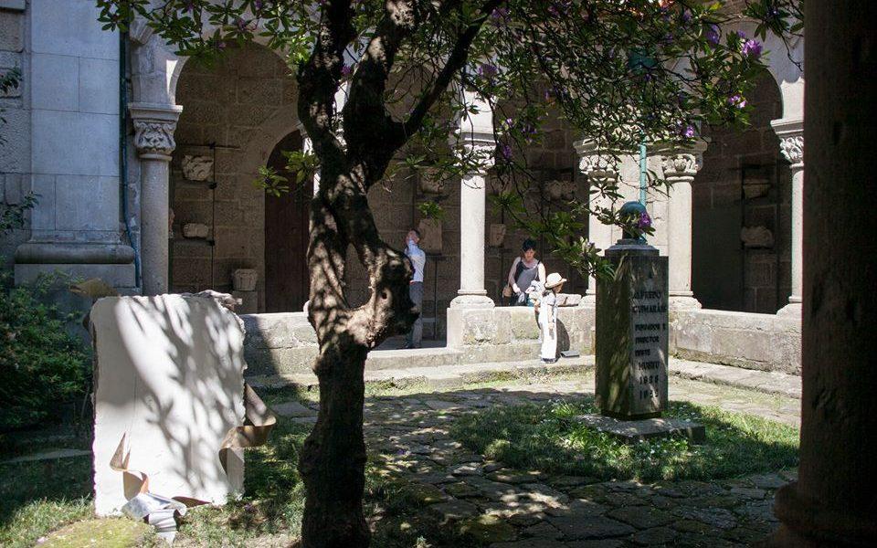 Área nororeste do claustro, com jardim e visitantes.