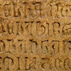 Inscrição em letra gótica. Pormenor da placa da fundação da Igreja da Oliveira. Século XIV: