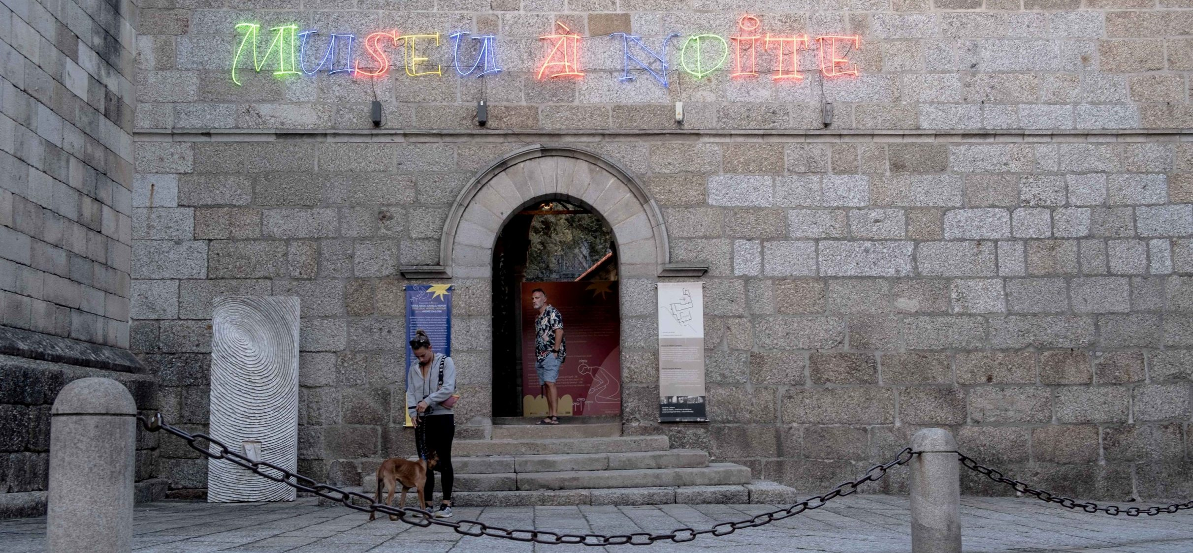 Entrada lateral do Museu Alberto Sampaio. Portal de ferro forjado com as letras 'Museu à Noite'.